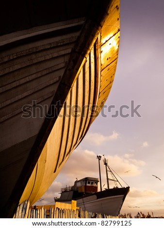Essaouira, Morocco: Wooden hull of boat at sunset in shipyard dry-dock, Essaouira, Morocco - stock photo
