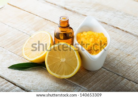 Essential aroma oil and sea salt with lemon on wooden background. Selective focus. - stock photo