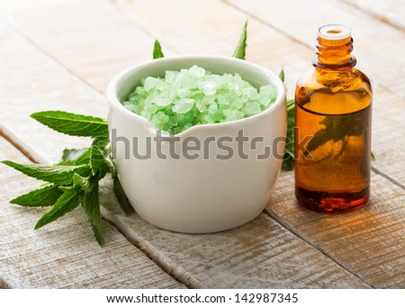 Essential aroma oil and sea salt with mint on wooden background. Selective focus. - stock photo