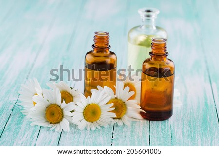 Essential aroma oil with chamomile on wooden background. Selective focus, horizontal. - stock photo