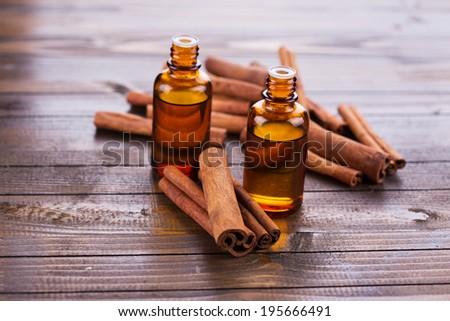 Essential aroma oil with cinnamon  on wooden background. Selective focus. - stock photo