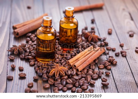 Essential aroma oil with coffee and spices on wooden background. Selective focus. - stock photo