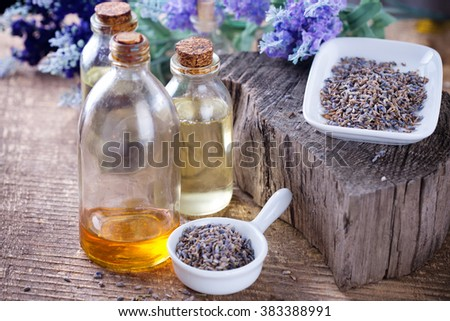 Essential aroma oil with lavender  on wooden background. Selective focus is on right bottle. - stock photo