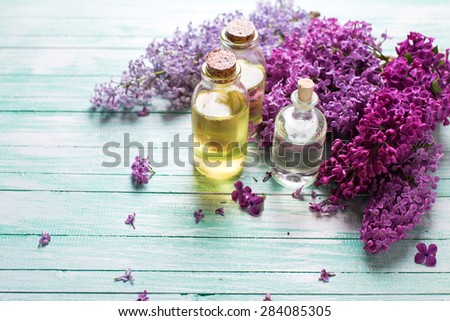 Essential aroma oil with lilac on  turquoise painted wooden background. Selective focus. Place for text. - stock photo