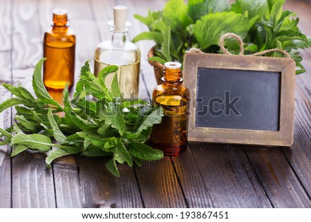 Essential aroma oil with peppermint  and empty blackboard on wooden background. Selective focus, horizontal. - stock photo
