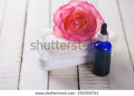 Essential aroma oil with rose on wooden background. Spa set?iing. Selective focus. - stock photo