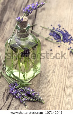 essential herbal lavender oil with fresh flowers on wooden background. selective focus - stock photo