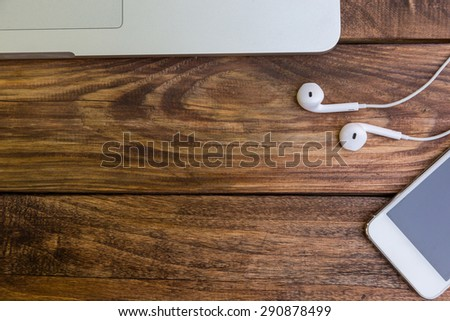 Essential items on wooden desk. Grey metallic cropped laptop white smart phone headphones located on rough natural handcrafted wood background top view - stock photo