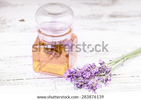 Essential lavender oil and fresh lavender flowers on a background - stock photo