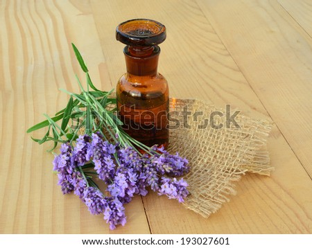 Essential lavender oil with fresh flowers on wooden background. - stock photo