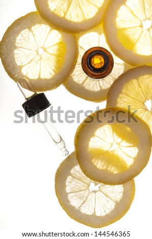 Essential oil amber glass bottle with dropper and some slices of lemon - stock photo