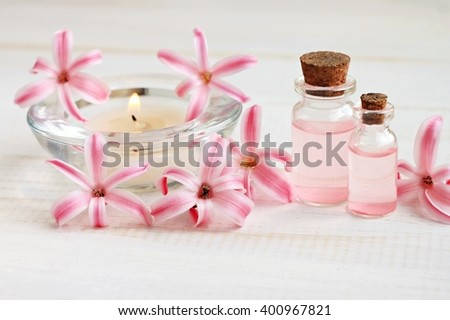 Essential oil and aroma candle with fresh hyacinth flower decor. Soft focus.  - stock photo