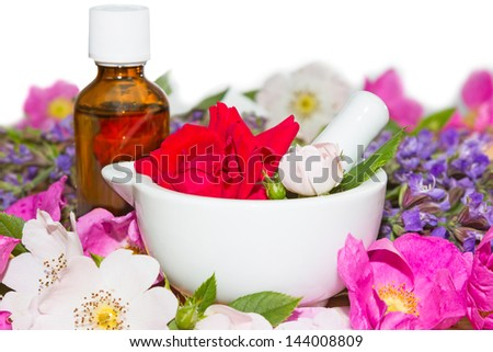 Essential oil and rose blossoms in mortar used in aromatherapy and spa - stock photo
