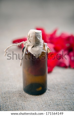 Essential oil bottle and red roses, perfume water - stock photo