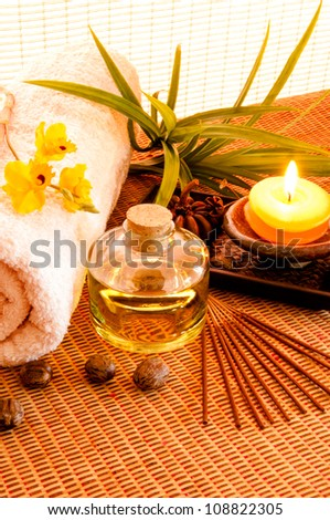 Essential oil bottles, towels, candle and flower in health spa for spa treatment. - stock photo