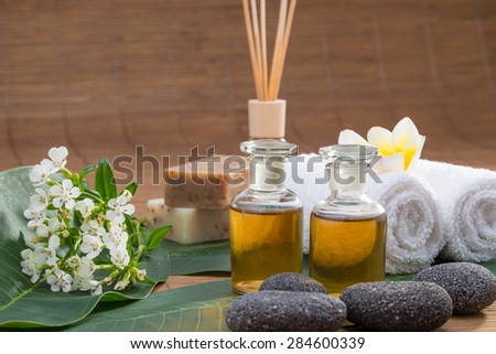Essential Oil, flower, pebble stone on green leaf, white towel, blur background for spa - stock photo