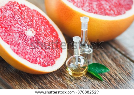 Essential oil in glass bottle with fresh, juicy grapefruit and green leaves-beauty treatment. Spa concept. Selective focus. - stock photo