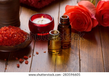 Essential oil, Mineral bath salts, candle and flowers on the brown  wooden table. - stock photo