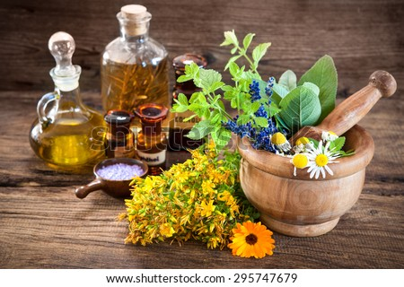 Essential oil, mortar with fresh herbs and bath salt on wooden background - stock photo
