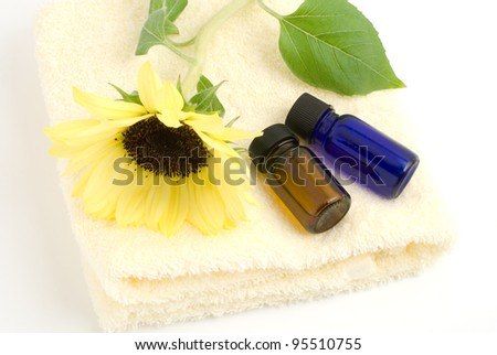 Essential oil on the yellow towel with sunflower on white background - stock photo