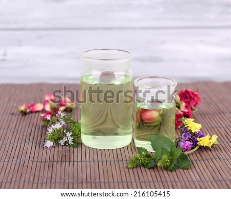 Essential oil with different medicine plants, on wooden background - stock photo