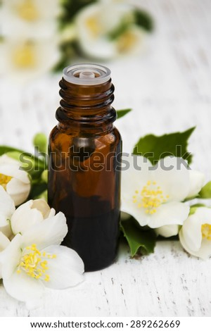 essential oil with jasmine flower on a wooden background