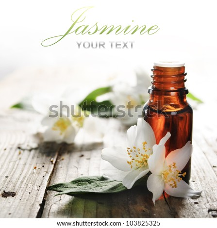 Essential oil with jasmine flower on wooden plank - stock photo
