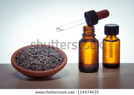 essential oil with lavender flowers - stock photo