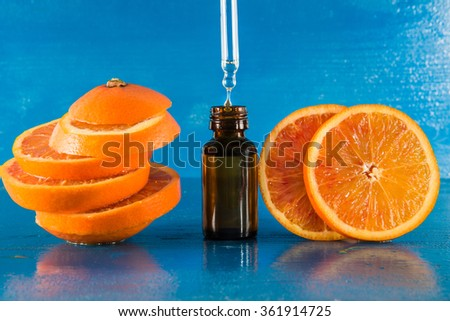Essential oil with orange slices, bottle and dropper, with blue background (horizontal) - stock photo