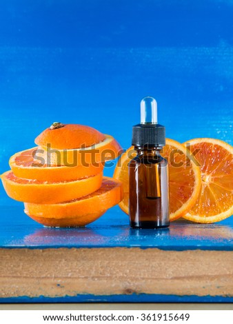 Essential oil with orange slices, bottle and dropper, with blue background (vertical)  - stock photo