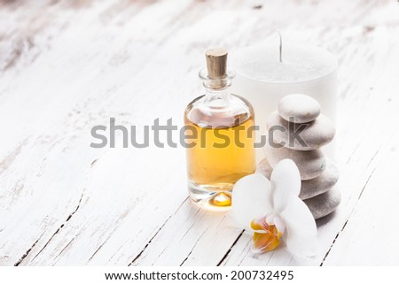 essential oil with orchid flower, candle and stones - spa concept - stock photo