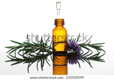 Essential oil with rosemary flowers - stock photo