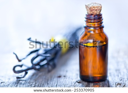 Essential oil with vanilla on a table - stock photo