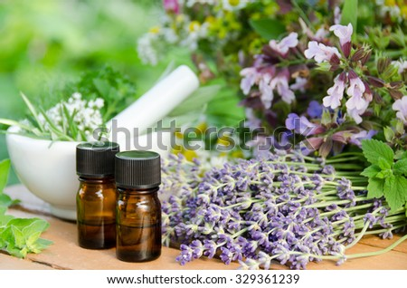 essential oils and a mortar with herbs - stock photo