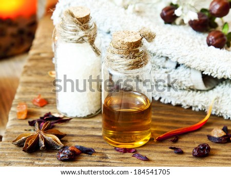 Essential Oils Bottles for Aromatherapy.Spa Setting with Towel and Anise - stock photo