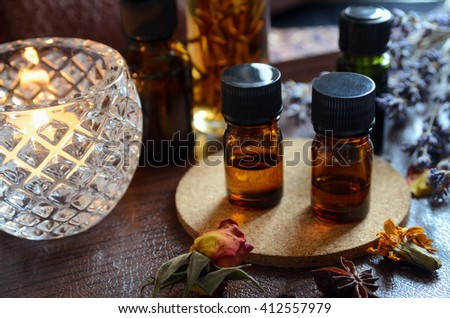 essential oils for aromatherapy treatment in candle light - stock photo