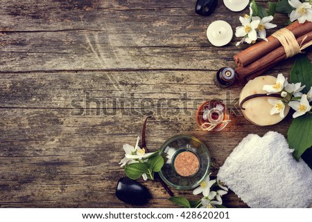 Essential oils with jasmine, cinnamon and vanilla on rustic wooden table, retro style image. - stock photo
