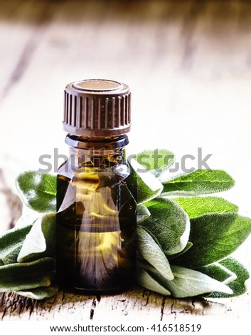 Essential sage oil, for aromatherapy, fresh sage leaves, vintage wooden background, selective focus
