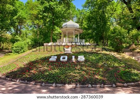 ESSENTUKI, RUSSIA - MAY 22 2015: Flower calendar with Essentuki inscription and 'Sluchainaya vstrecha' pavilion at Kurortny (Glavny) park - stock photo