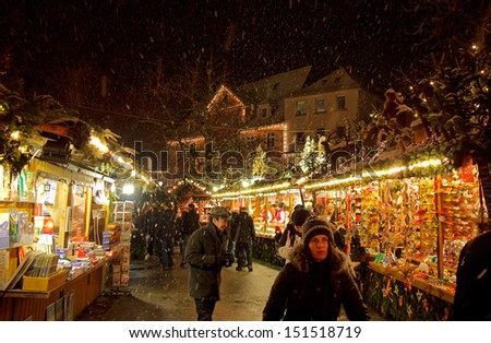 ESSLINGEN, GERMANY - DEC 11TH, 2012: People stroll down an aisle at the Christmas Market at night circa December 2012 in Esslingen. Esslingen is famous for its annual medieval Christmas Market.