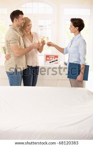 Estate agent and couple celebrating deal of buying new house. - stock photo