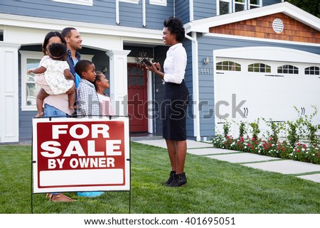 Estate agent and family outside house with a â??for saleâ?? sign