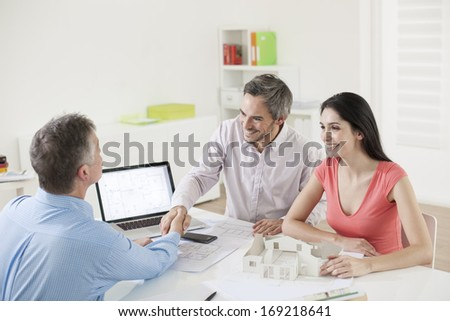 Estate agent congratulating couple - stock photo