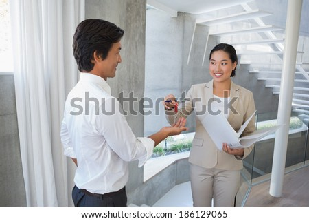 Estate agent giving house key to buyer in the hallway