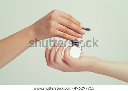 estate agent giving house key with a keychain to female buyer hand