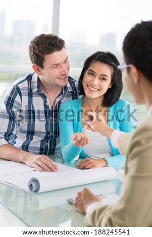 Estate agent giving keys to the young lady - stock photo