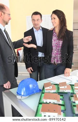 Estate agent handing keys to couple - stock photo