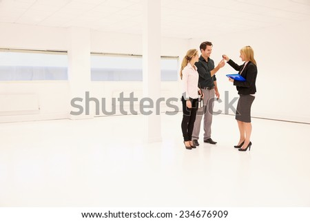 Estate Agent Handing Over Keys To Office Space - stock photo