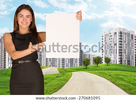 Estate agent holding blank poster with city on background. New houses and green grass - stock photo