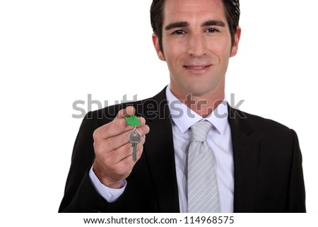 Estate agent holding house key - stock photo